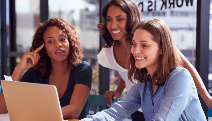 Three Businesswomen With Laptop At Desk By Window In Office Collaborating On Project Together